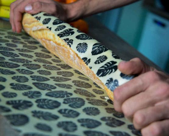 Beewrap XXL motif feuille et sa baguette en cours d'emballage