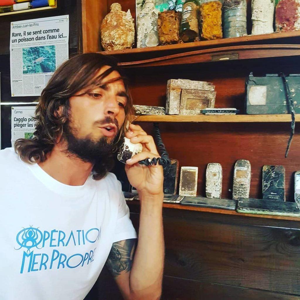 Guillaume au téléphone (de récupération) dans le musée des objets récupérés par Opération Mer Propre