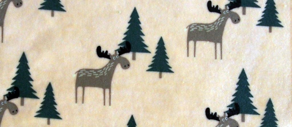 Des couleurs pour l'hiver : motif de bee wrap avec un élan dans une forêt de sapins